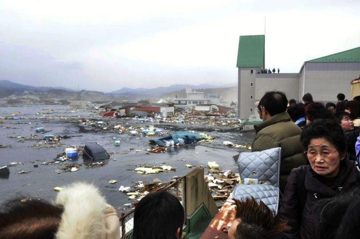 (Foto: Los residentes locales contemplar la devastación después de una ola de marea del tsunami en la ciudad de Kesennuma en la prefectura de Miyagi, al norte de Japón el 11 de marzo de 2011 por Yomiuri Shimbun / STR / AFP / Getty Images..)